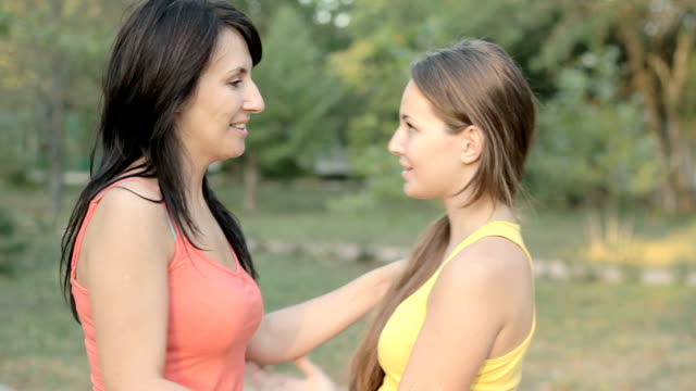 vídeos de stock e filmes b-roll de mãe e filha a conversar ao ar livre no parque de verão - filha