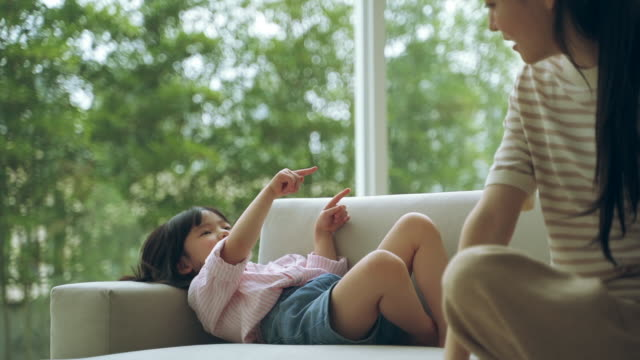 mother and daughter talking to each other on the sofa - kindertag stock-videos und b-roll-filmmaterial