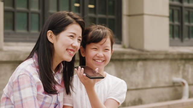 mother and daughter talking together on the phone - taipei stock videos & royalty-free footage