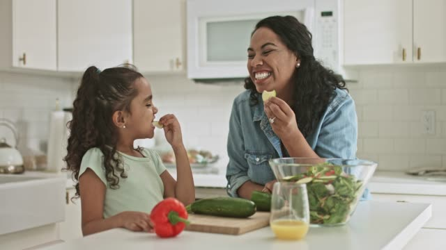 mother and daughter tasting some zucchini food while preparing food at home - healthy eating stock videos & royalty-free footage