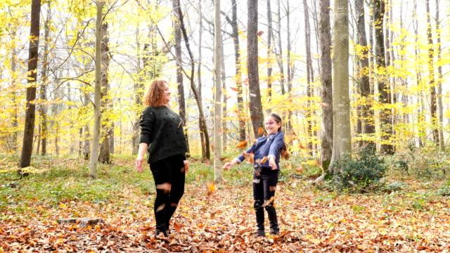母と娘。空気中の葉を投げる