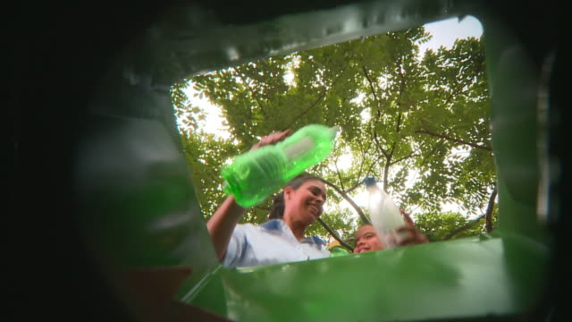 vidéos et rushes de pov la ms mother and daughter (8-9) throwing plastic bottles into garbage bin, panama city, panama  - bouteille