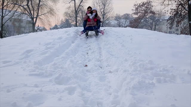 Mother and daughter tobogganing