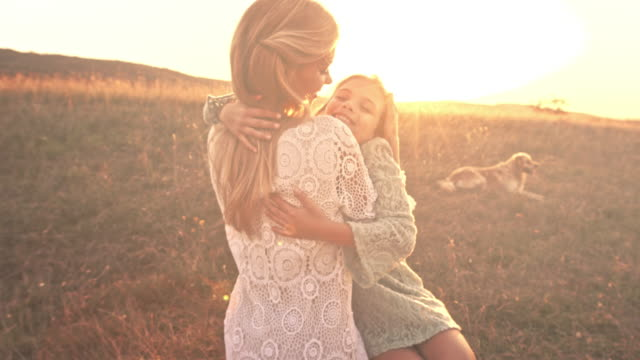 Mother and daughter together at sunset