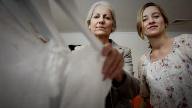 ms mother and daughter together shopping for new outfits looking through clothing rack / new york city, new york, usa - adult offspring stock videos & royalty-free footage