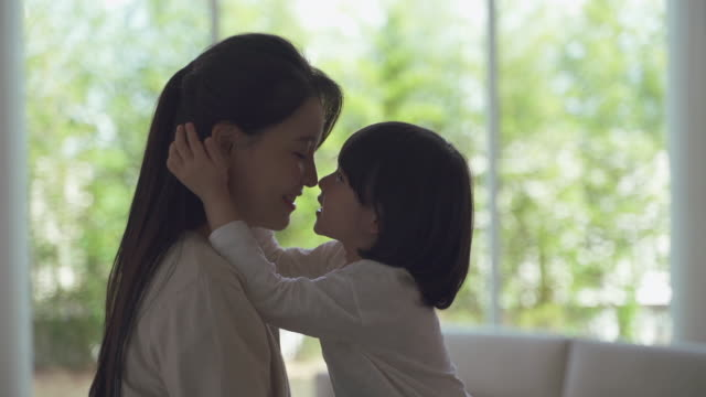 mother and daughter touching noses together in the living room - korean ethnicity stock videos & royalty-free footage