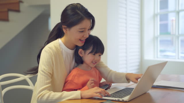 mother and daughter using a computer at a table - kindertag stock-videos und b-roll-filmmaterial