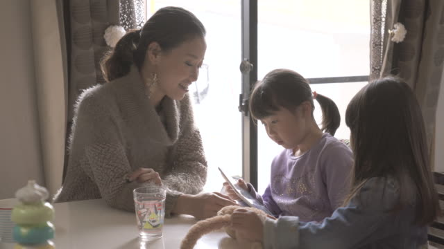 mother and daughter using a digital tablet in the room - living room点の映像素材/bロール