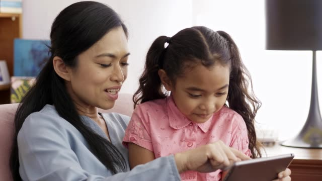 mother and daughter using digital tablet at home - malaysian ethnicity stock videos & royalty-free footage