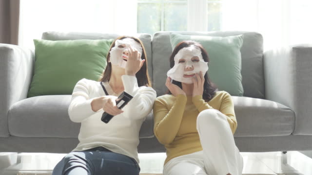 mother and daughter using face mask sheets and watching a tv - beauty treatment stock videos & royalty-free footage
