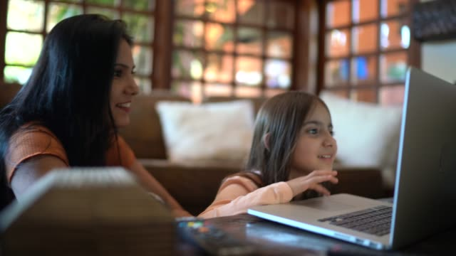 mother and daughter using laptop at home - stream stock videos & royalty-free footage