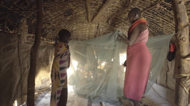 mother and daughter using mosquito net. kenya. africa. - netting stock videos & royalty-free footage
