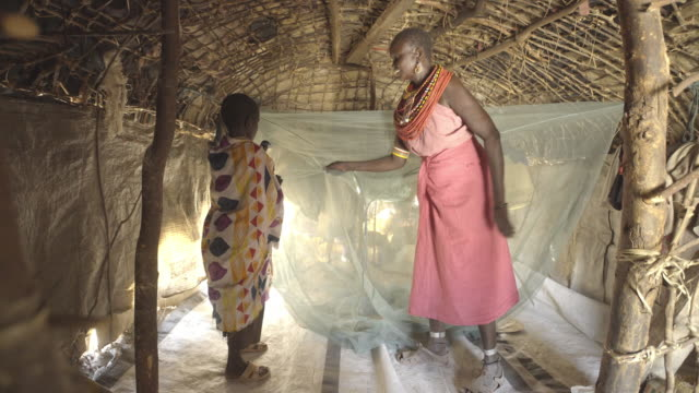 mother and daughter using mosquito net. kenya. africa. - 遊牧民族点の映像素材/bロール