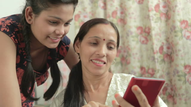 mother and daughter using phablet together in domestic room. - indian ethnicity stock videos and b-roll footage