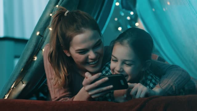 vídeos de stock e filmes b-roll de mother and daughter using phone - tenda estrutura feita pelo homem