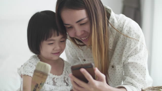 Mother And Daughter Using Smart Phone In Bedroom