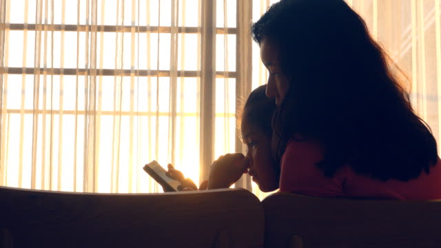 mother and daughter using smartphone at home - hugging self stock videos & royalty-free footage