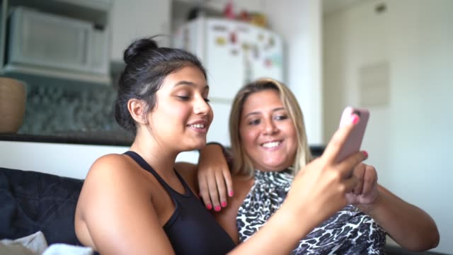 mother and daughter using smartphone while they are sitting on the sofa - latin american and hispanic ethnicity stock videos & royalty-free footage