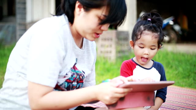 mother and daughter using tablet. - hugging self stock videos & royalty-free footage