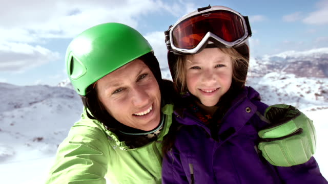 slo mo mother and daughter video selfie on ski slope - winter sport stock videos and b-roll footage