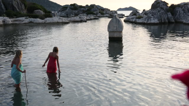 mother and daughter wade out to a partially sunken sarcophagus - wearing a towel stock videos and b-roll footage