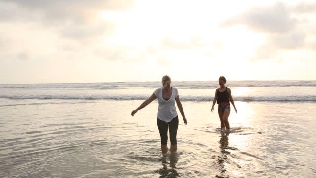 vídeos de stock e filmes b-roll de mother and daughter walk along tidal flats from gentle surf - filha