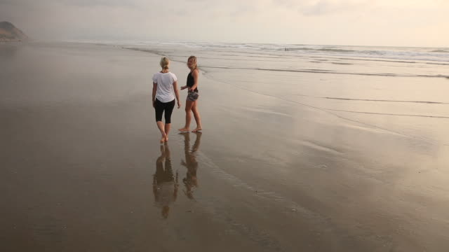 Mother and daughter walk along tidal flats towards horizon