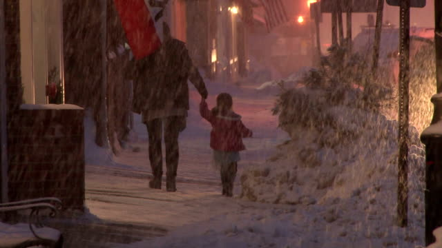A mother and daughter walk down the street as a blizzard takes aim at New England
