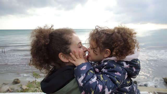 vídeos de stock, filmes e b-roll de mãe e filha caminhando sozinhas na natureza, mãe e filha caminhando na praia, mãe e filha se beijando, menina encaracolada escreve ficar em casa na areia e dá uma mensagem social, conceito de família feliz e infância - cabelo encaracolado