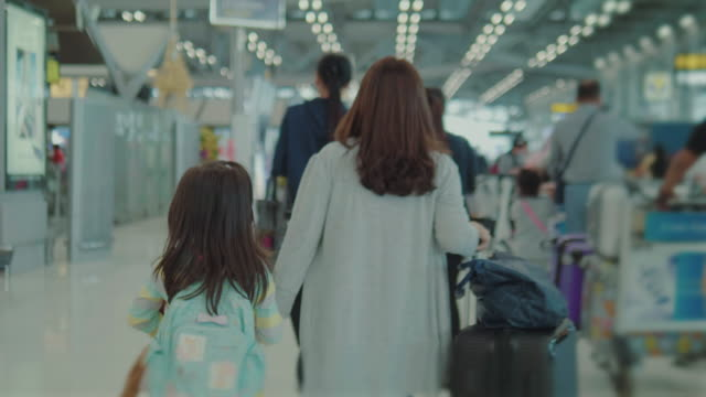 mother and daughter walking at airport. - station stock videos & royalty-free footage