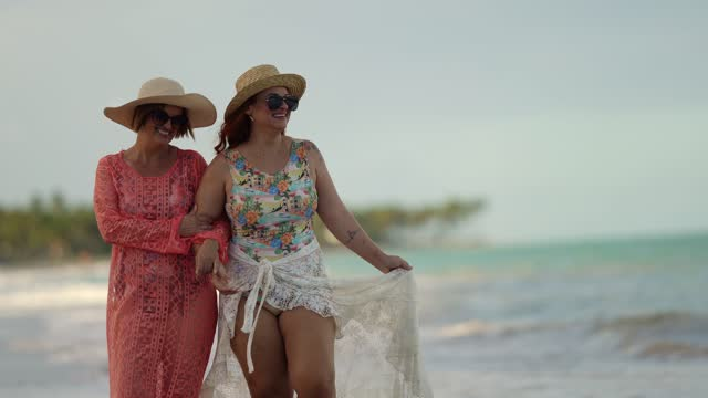 mother and daughter walking hand in hand on the beach - swimming costume stock videos & royalty-free footage