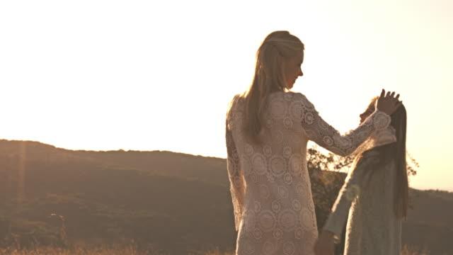 母と娘の日没で自然の中を歩いて