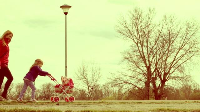 stockvideo's en b-roll-footage met mother and daughter walking in park with doll stroller - kleurtoon