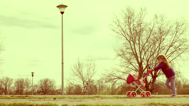 mother and daughter walking in park with doll stroller - eastern european culture stock videos & royalty-free footage