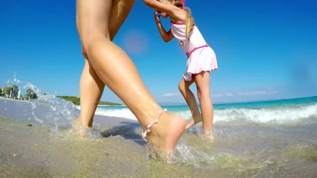 Mutter und Tochter zu Fuß am Strand mit Wellen Nähern