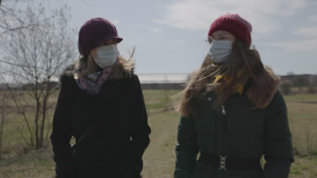 mother and daughter walking on spring day during covid-19 pandemic - warm clothing stock videos & royalty-free footage