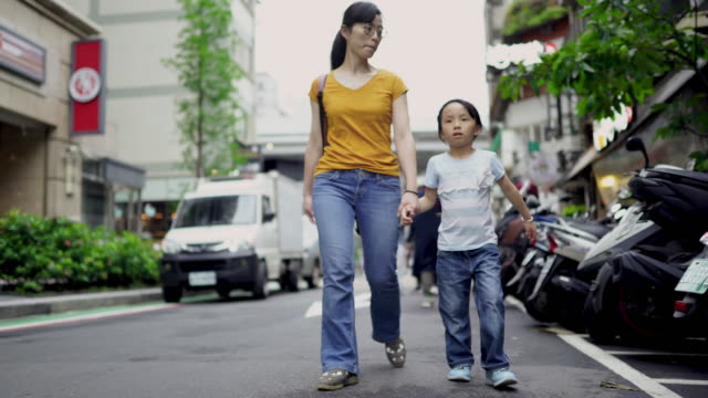 mother and daughter walking on the street of taipei - rucksack stock videos & royalty-free footage