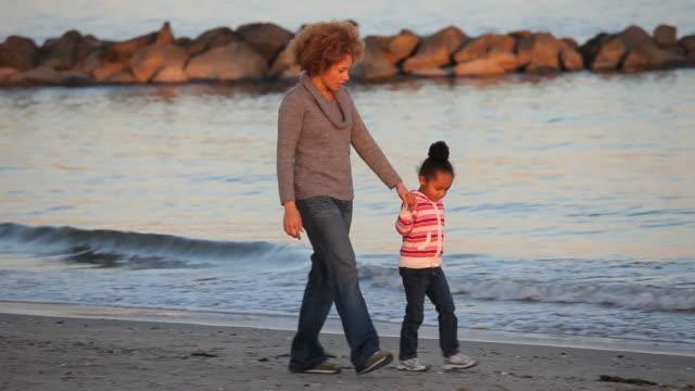 ws pan mother and daughter (4-5) walking on virginia beach, picking up shells / virginia, usa - virginia beach stock videos & royalty-free footage