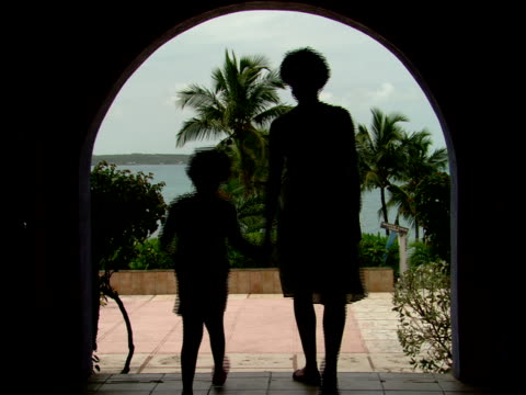 stockvideo's en b-roll-footage met ms,  mother and daughter (8-9 years) walking through archway overlooking sea,  rear view,  harbour island,  bahamas - waaierpalm