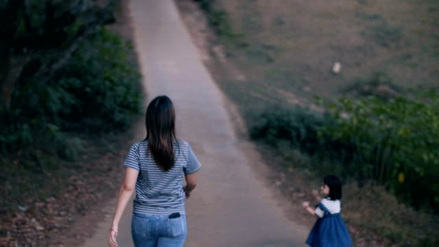 Mother and daughter walking together in public park