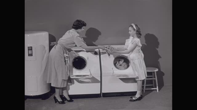 ms mother and daughter washing clothes in washing machine / united states - 1950点の映像素材/bロール