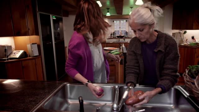 vídeos de stock e filmes b-roll de ms mother and daughter washing vegetables in sink / kingston, new york, usa  - filha