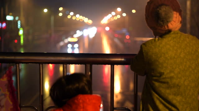 mother and daughter watch in excitement as fireworks go off all around them in the rain. focus on family. - 春節点の映像素材/bロール