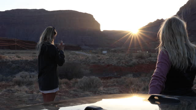 mother and daughter watch sunset beside vehicle - moab utah stock videos & royalty-free footage