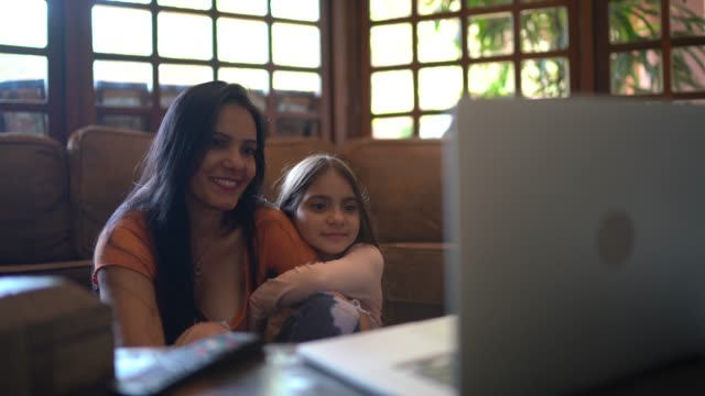 mother and daughter watching a movie or video on laptop at home - daughter stock videos & royalty-free footage
