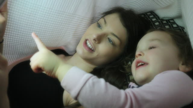 mother and daughter watching bedtime story videos - bedtime stock videos & royalty-free footage