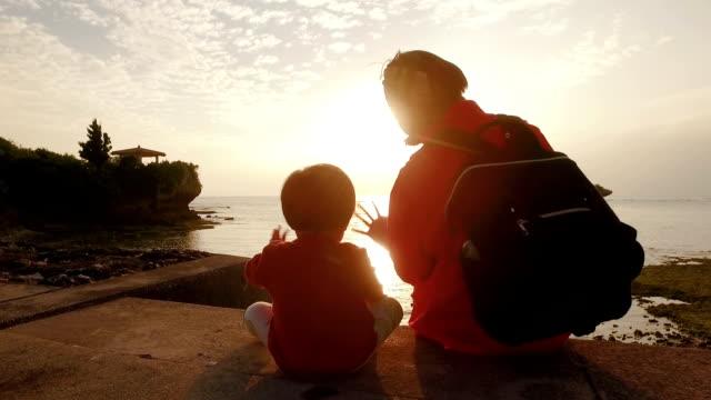 母と娘の夕日を見てします。