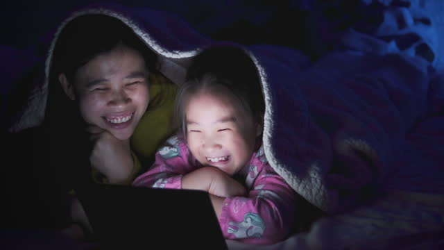 mother and daughter watching tablet in bed room at night time - bedtime stock videos & royalty-free footage