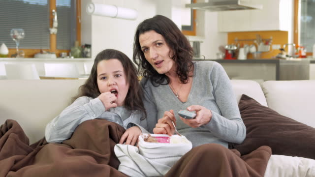 hd dolly: mother and daughter watching tv - ice cream stock videos & royalty-free footage