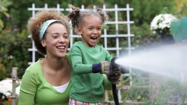pan mother and daughter watering plants in vegetable garden / richmond, virginia, usa - giardinaggio video stock e b–roll